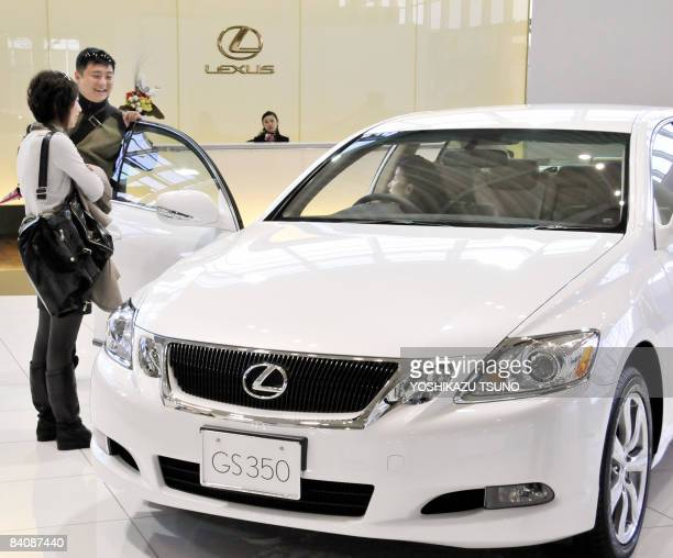 Customers check a Lexus vehicle at a Toyota showroom in Tokyo on December 19 2008 Japan's auto giant Toyota Motor is likely to suffer its firstever...