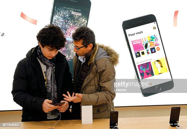 Customers check an iPhone 7 inside the new Apple store SaintGermain during the first opening day on December 03 2016 in Paris France This store...