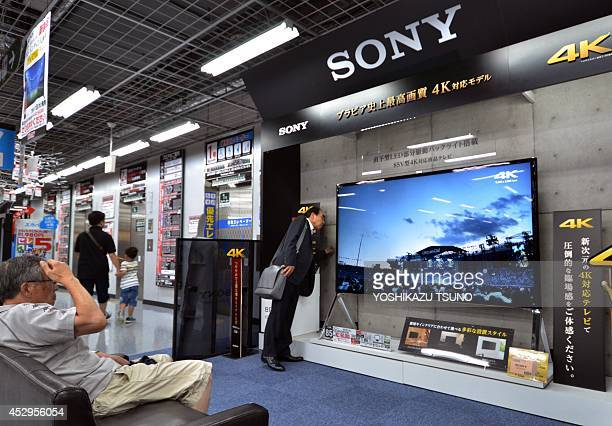 Customers check Japan's electronics giant Sony's 4K LCD television set at an electric shop in Tokyo on July 31 2014 Sony said it posted a 261 million...