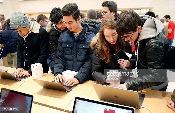Customers check the new MacBook Pro laptop computer inside the new Apple store SaintGermain during the first opening day on December 03 2016 in Paris...