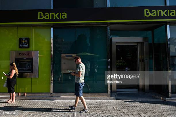 Customers check their bank account passbooks outside a Bankia SA branch in Tarragona Spain on Wednesday Sept 4 2013 Bankia is set to agree the sale...