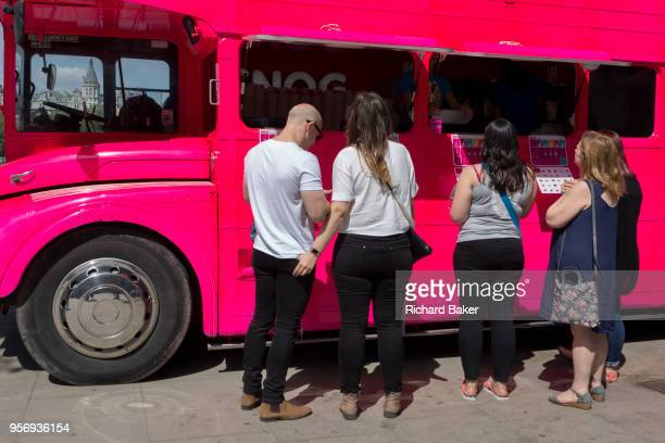 Customers choose what to buy from the pink doubledecker Routemaster bus of yoghurt retailer Snog on the Southbank on 9th May 2018 in London England