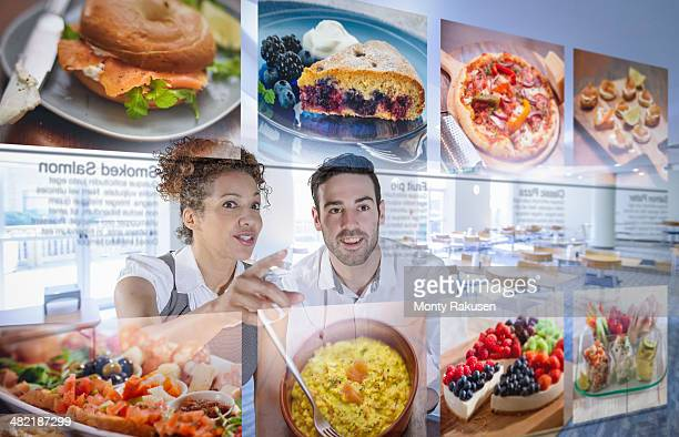 Customers choosing food from interactive display in office canteen