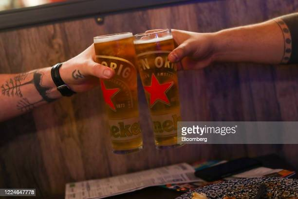 Customers clink pints of beer at The Moon Under Water pub, operated by J D Wetherspoon Plc, on Leicester Square in London, U.K., on Saturday, July 4,...
