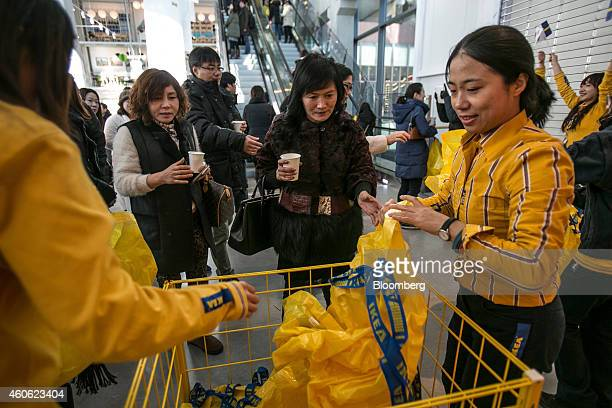 Customers collect Ikea AB shopping bags from employees during the opening of the company's store in Gwangmyeong Gyeonggi province South Korea on...