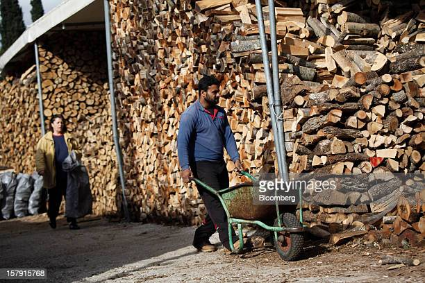Customers collect wood logs to use as heating fuel from a firewood supply store in Athens Greece on Friday Dec 7 2012 Greece the epicenter of...