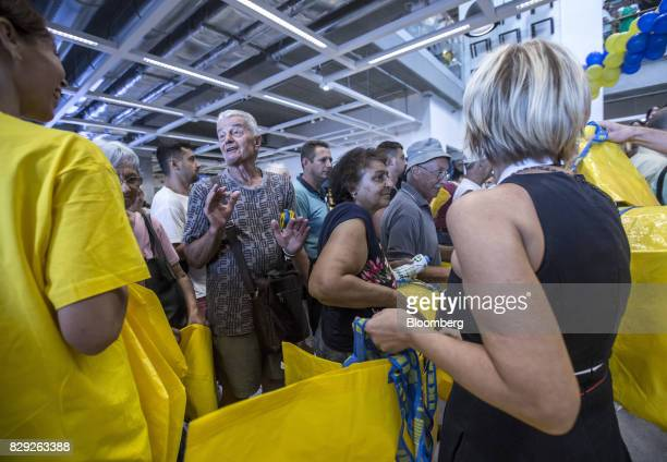 Customers collect yellow IKEA shopping bags on the opening day of IKEA of Sweden AB's first department store in Belgrade Serbia on Thursday Aug 10...