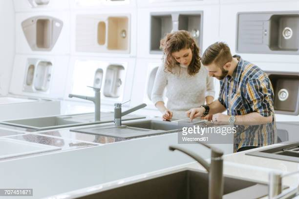 customers consulting saleswoman in shop for kitchen sinks - showroom stock pictures, royalty-free photos & images