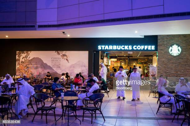 Customers consume food and drink on the terrace of a Starbucks Corp coffee shop in Avenues shopping mall in Kuwait City Kuwait on Sunday Aug 13 2017...