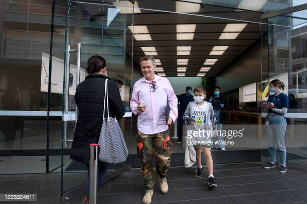 Customers depart the Apple Store at Bondi Junction on May 07, 2020 in Sydney, Australia. Apple stores across Australia reopened today, after closing...