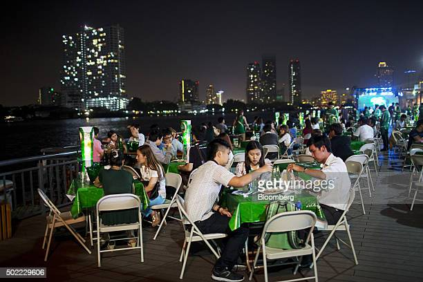Customers dine at a restaurant on the waterfront at Asiatique The Riverfront openair mall in Bangkok Thailand on Friday Dec 18 2015 Thai economic...