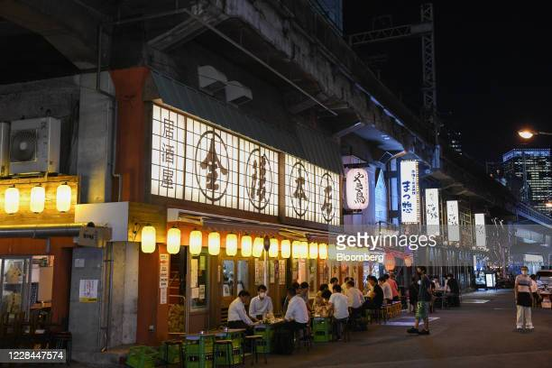 Customers dine at an izakaya restaurant built under railway tracks in Tokyo, Japan, on Tuesday, Sept. 8, 2020. In Tokyo, the spaces beneath elevated...