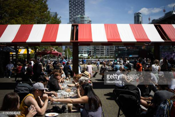 Customers dine at tables outside the Granville Island Public Market in Vancouver British Columbia Canada on Sunday June 2 2019 Statistics Canada is...