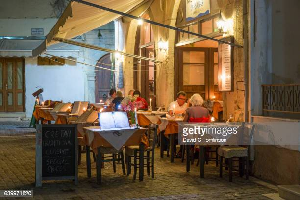 Customers dining on illuminated terrace of a traditional taverna, Rethymno, Crete, Greece