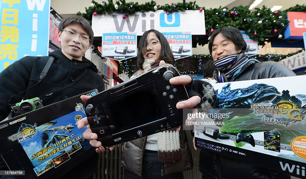 Customers display their purchases after buying Japanese electronics titan Nintendo's new videogame console 'Wii U' at a shop in Tokyo on December 8, 2012. Nintendo released the new console in Japan on December 8 and is hoping for a repeat of the runaway success it had with original Wii consoles, which lured legions of 'casual gamers' into the videogame world with the introduction of motion-sensing controls. AFP PHOTO/Toru YAMANAKA