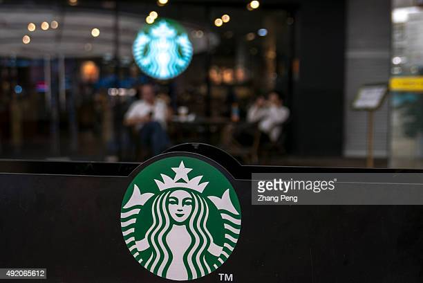 Customers drink coffee outside a Starbucks cafe. Starbucks is streamlining the ordering process so customers are able to get that cup of coffee...