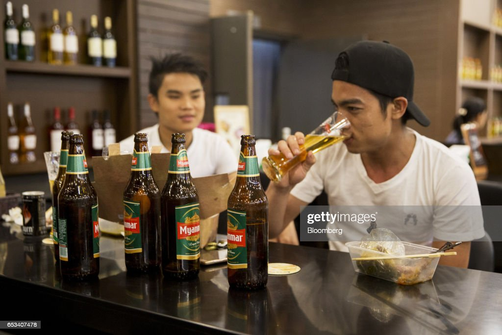 Customers drink Myanmar Beer, manufactured by Myanmar Brewery Ltd., at a bar inside a Marketplace by City Mart store, operated by City Mart Holdings Co., in Yangon, Myanmar, on Saturday, March 11, 2017. City Mart has 20 years of market knowledge to help it compete against international players, said Win Win Tint, managing director of City Mart in a Bloomberg interview on March 9. Photographer: Brent Lewin/Bloomberg via Getty Images