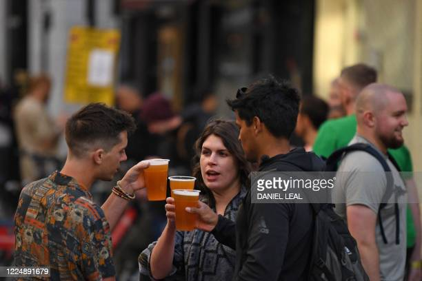 Customers drink out of plastic glasses outside re-opened bars in Soho in London on July 5 as the Soho area embraces pedestrianisation in line with an...