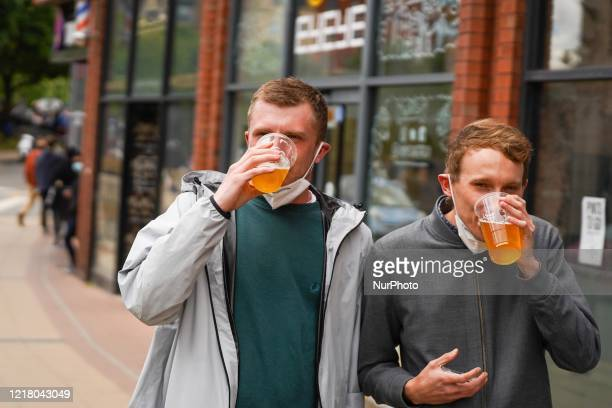 Customers drink their takeaway draught beer in plastic cups outside a pub in Sheffield , on 6 June 2020