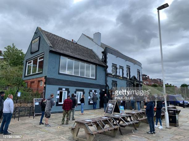 Customers drink their take-away draught beer served in plastic cups, outside 'The Ferry' pub, overlooking the river Mersey in Egremont, on the Wirral...
