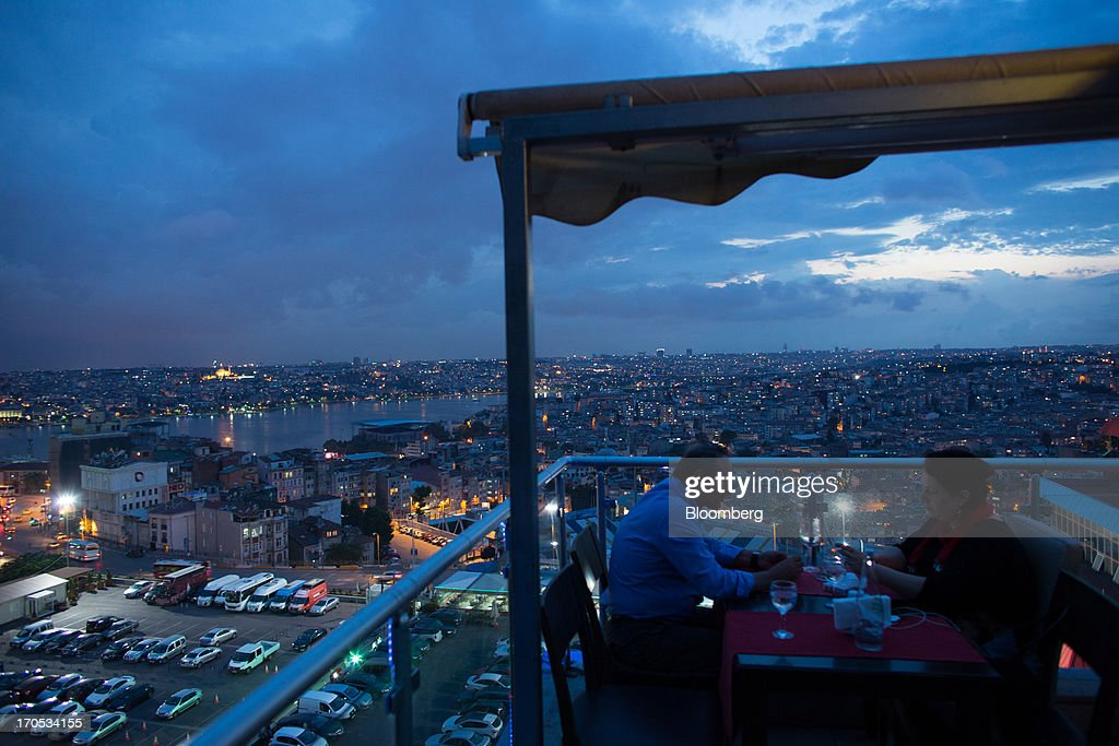 Customers eat an evening meal at a rooftop restaurant overlooking the illuminated skyline of Istanbul, Turkey, on Thursday, June 13, 2013. The law forbids the sale of alcohol at night and near schools and mosques, going against the secular traditions of the Muslim-majority country of 74 million, where many people drink and women often choose not to cover their hair. Photographer: Lam Yik Fei/Bloomberg via Getty Images