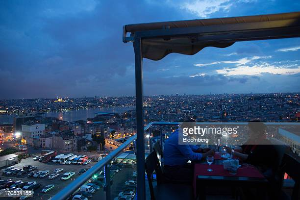 Customers eat an evening meal at a rooftop restaurant overlooking the illuminated skyline of Istanbul, Turkey, on Thursday, June 13, 2013. The law...