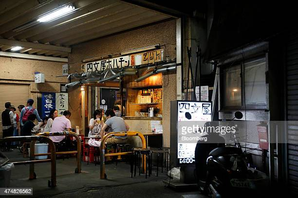 Customers eat and drink at tables outside a restaurant at night in the Koenji district of Tokyo Japan on Sunday May 24 2015 Japan's Topix index fell...