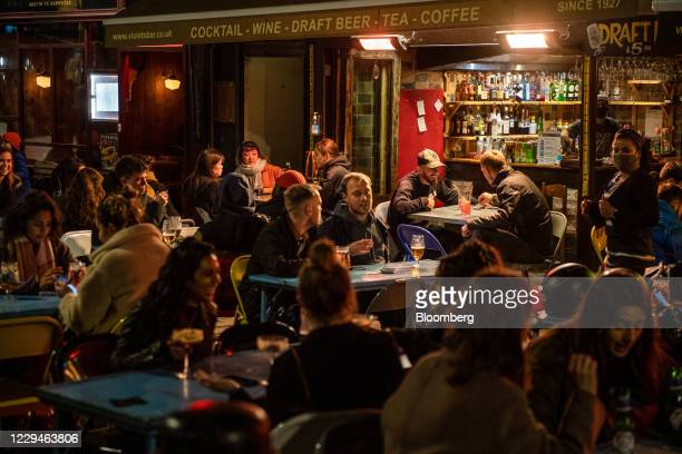 Customers eat and drink on the street outside a bar in the Soho district, ahead of a coronavirus lockdown, in London, U.K., on Wednesday, Nov. 4,...