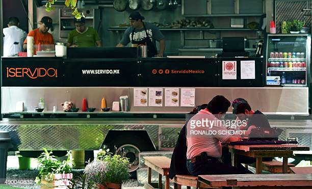 Customers eat as employees work at a food truck in Mexico City on September 15 2015 With its street food culture Mexico City distills fried food...