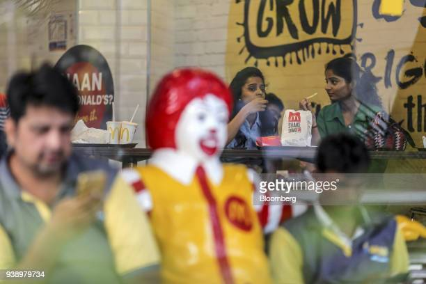 Customers eat as food delivery couriers sit next to a statue of Ronald McDonald outside a McDonald's Corp restaurant operated by Hardcastle...