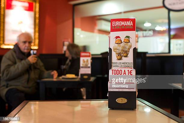 Customers eat at tables near promotional cards advertising one euro menus as part of 'Euromania' Wednesdays in a 100 Montaditos restaurant in Madrid...