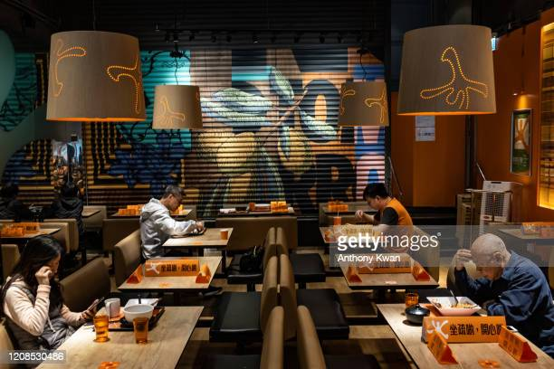 Customers eat in a restaurant with blocked seatings to make sure people adhere to social distancing on March 29, 2020 in Hong Kong, China. Hong Kong...