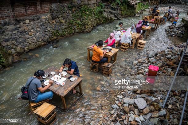 Customers eat lunch at a restaurant with tables in a stream of a river in Kampung Kemensah on the outskirts of Kuala Lumpur on July 14, 2020.