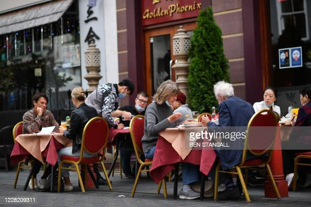 Customers eat lunch at the outside tables of a restaurant in the chinatown area of Soho in London on August 26 as businesses in the busy London area...