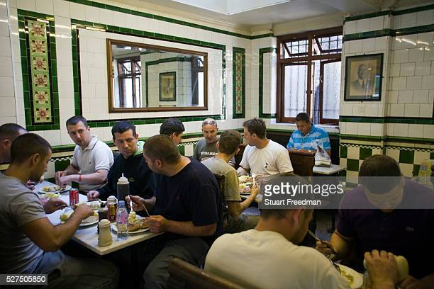 Customers eat lunch in Manze's Eel Pie and Mash shop on Tower Bridge Road London UKThis pie shop was opened in 1897 and is the oldest pie and eel...