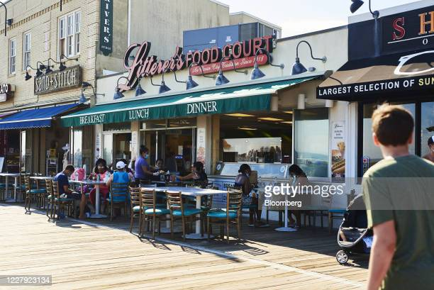 Customers eat outside at a restaurant on the boardwalk in Ocean City, New Jersey, U.S., on Saturday, Aug. 1, 2020. From California's wine country to...