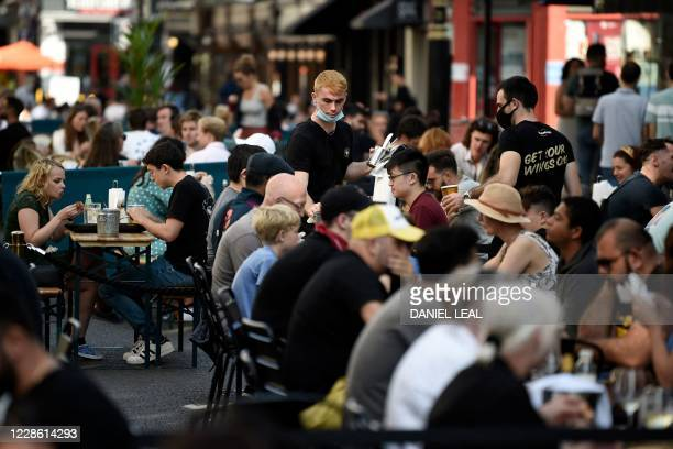 Customers eat sunday lunches at tables outside restaurants in Soho, in London on September 20, 2020 as the British government consider fresh...