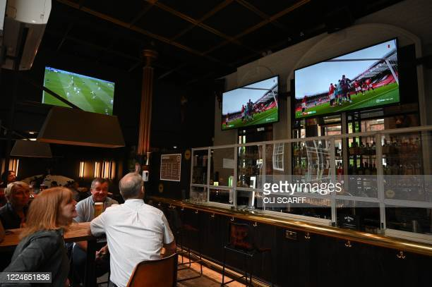 Customers enjoy a drink and watch the English Premier League football match between Manchester United and Bournemouth on television at The...