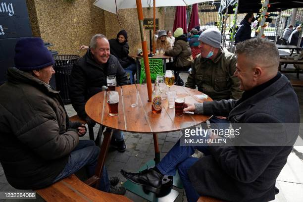 Customers enjoy a drink at an outside table after the Half Moon pub re-opened in east London as coronavirus restrictions are eased across the country...