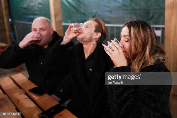 Customers enjoy a drink at the Switch bar in Newcastle shortly after midnight after the easing of lockdown measures on April 12, 2021 in Newcastle...