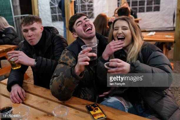 Customers enjoy a drink at the Switch bar in Newcastle shortly after midnight following the easing of lockdown measures on April 12, 2021 in...