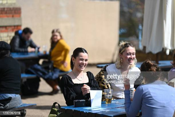 Customers enjoy a drink from The Terrace Bar at Alexandra Palace in north London on April 12, 2021 as coronavirus restrictions are eased across the...