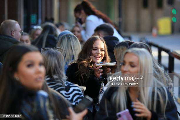 Customers enjoy a drink in the outside seating area of a pub in Leeds, northern England, on April 12, 2021 as coronavirus restrictions are eased...