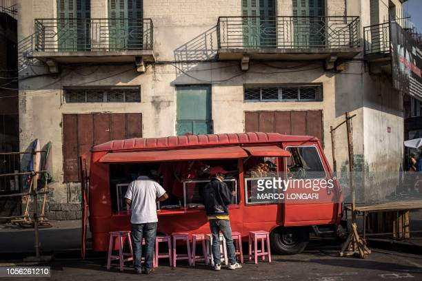 Customers enjoy breakfast at a market in central Antananarivo on November 2 2018 With a poverty rate of 762 percent Madagascar a former French colony...