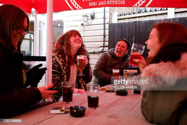 Customers enjoy drinks as the sit at an outside table at a re-opened pub in east London as coronavirus restrictions are eased across the country...