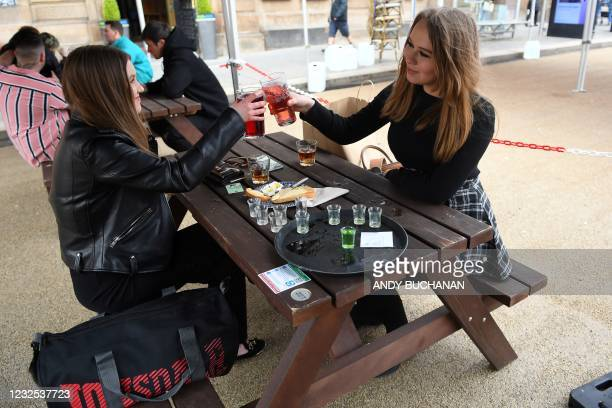 Customers enjoy drinks as they sit at an outside table at a re-opened Wetherspoons pub in Glasgow on April 26, 2021 following the relaxing of some...