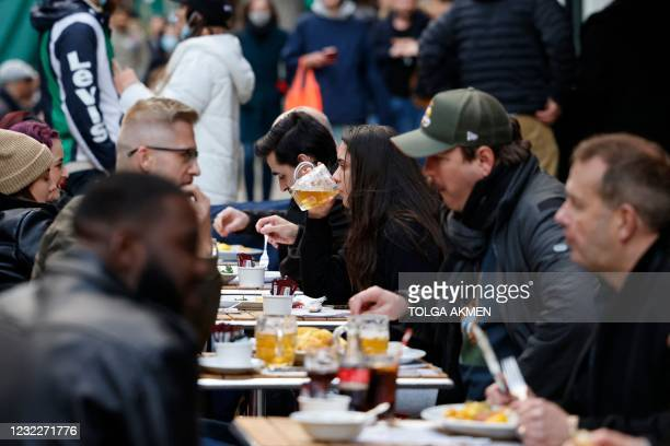 Customers enjoy drinks at tables outside the bars in the Soho area of London, on April 12, 2021 as coronavirus restrictions are eased across the...