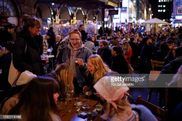 Customers enjoy drinks at tables outside the pubs and bars in the Soho area of London, on April 12, 2021 as coronavirus restrictions are eased across...