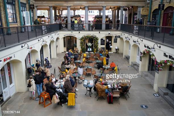 Customers enjoy food and drink at re-opened restaurants and cafes in Covent Garden in central London as coronavirus restrictions are eased across the...