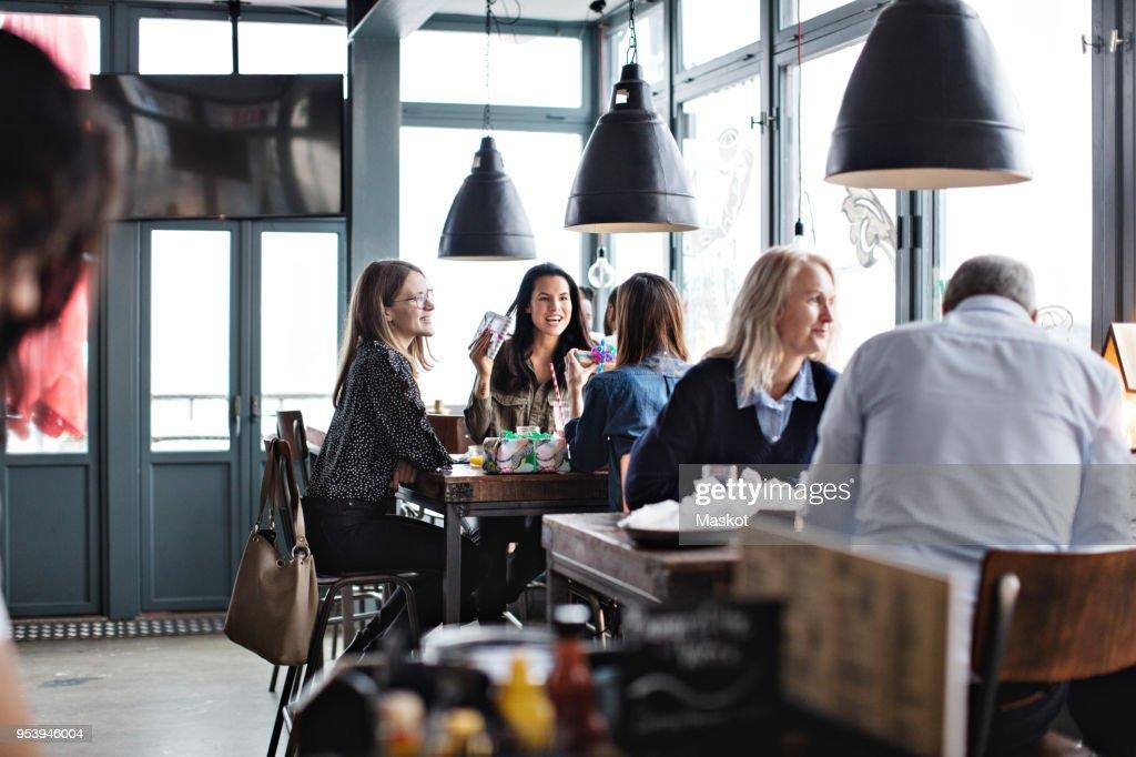Customers enjoying while sitting at restaurant : Stock-Foto
